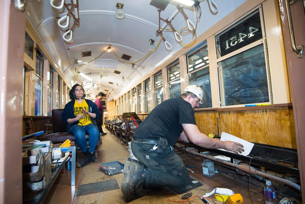 Man in hard hat, kneeling inside vintage transit car under repair .