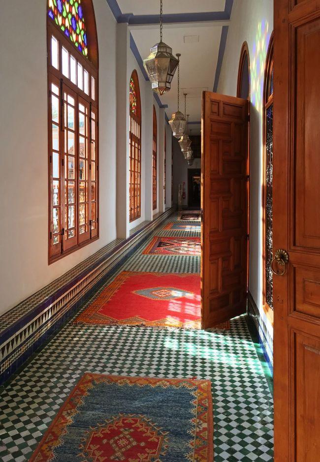 Des tuiles et des tapis colorés se marient avec des vitraux et des lampes dans les couloirs uniques du riad.