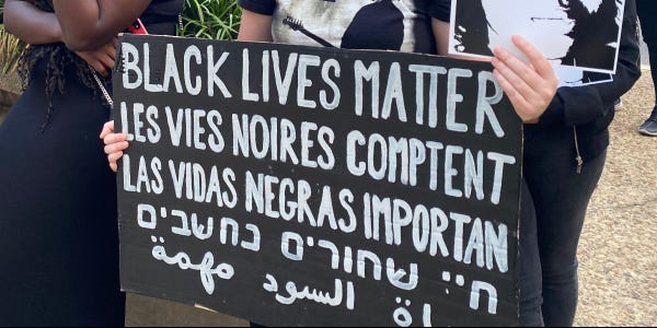 Photo of a handwritten protest sign that says BLACK LIVES MATTER in 5 different languages.