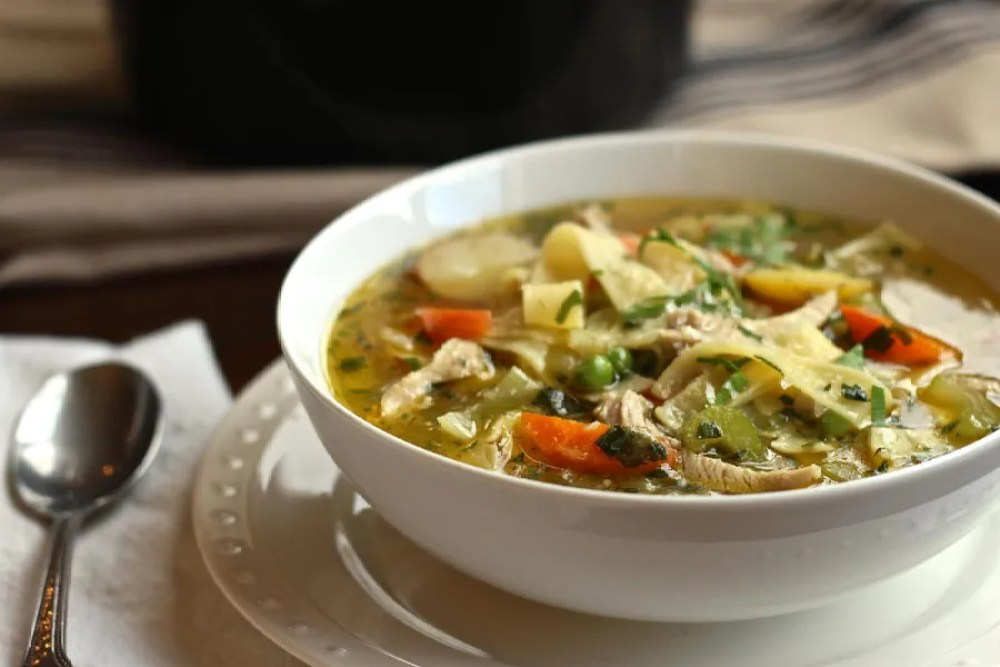 Chicken soup with egg noodles and petite peas