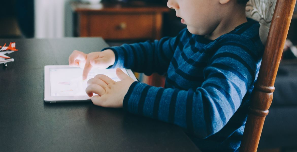 image of child typing on ipad screen