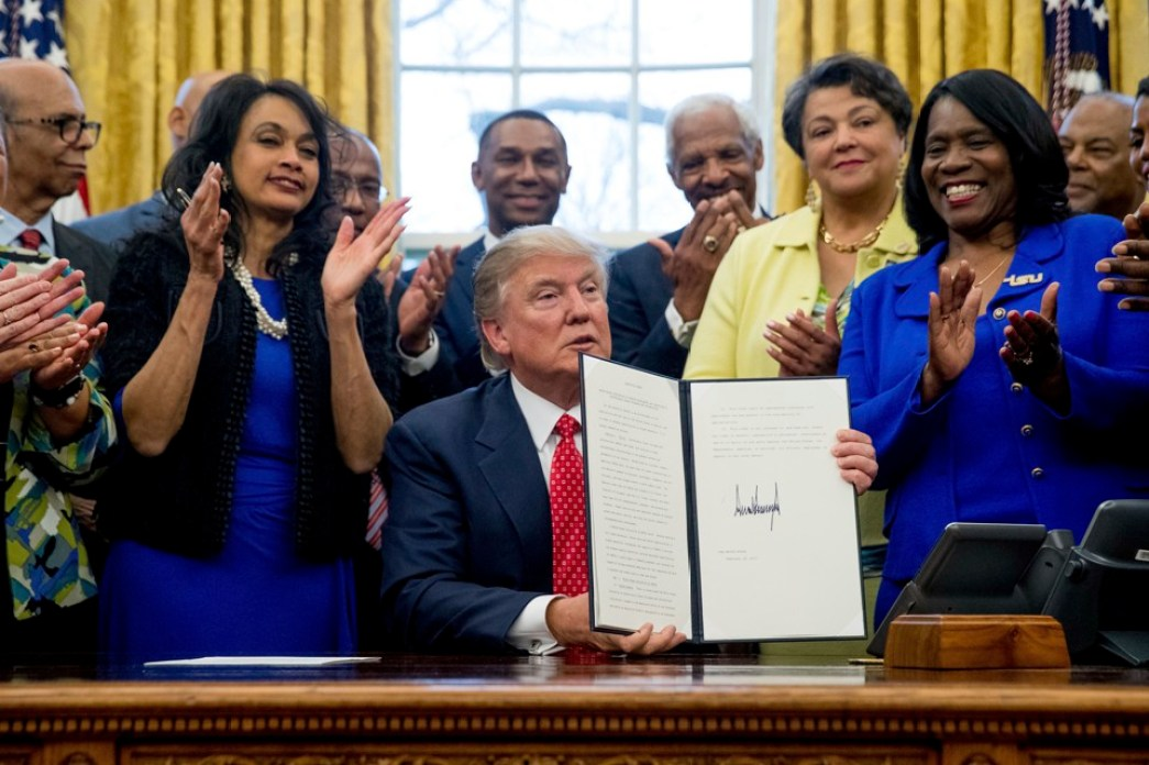 Donald Trump sits at his desk in the Oval Office holding a signed executive order. People smile and clap behind him.