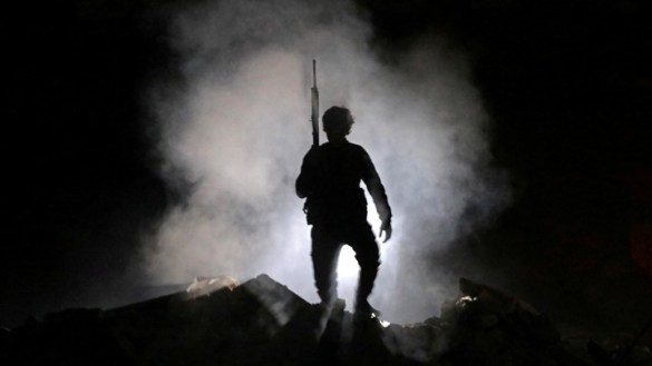 The Many Wars Within Syria s War   The Atlantic A fighter is cloaked by smoke as he holds up a weapon