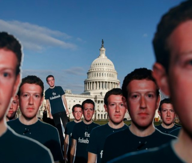 Cardboard Cutouts Of Mark Zuckerbergs Face Dominate The Foreground While The Dome Of The U S