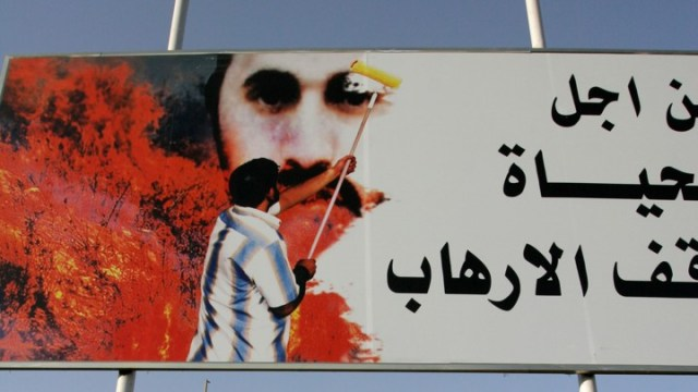 A poster in Baghdad depicts a man painting over a picture of Abu Musab al-Zarqawi.