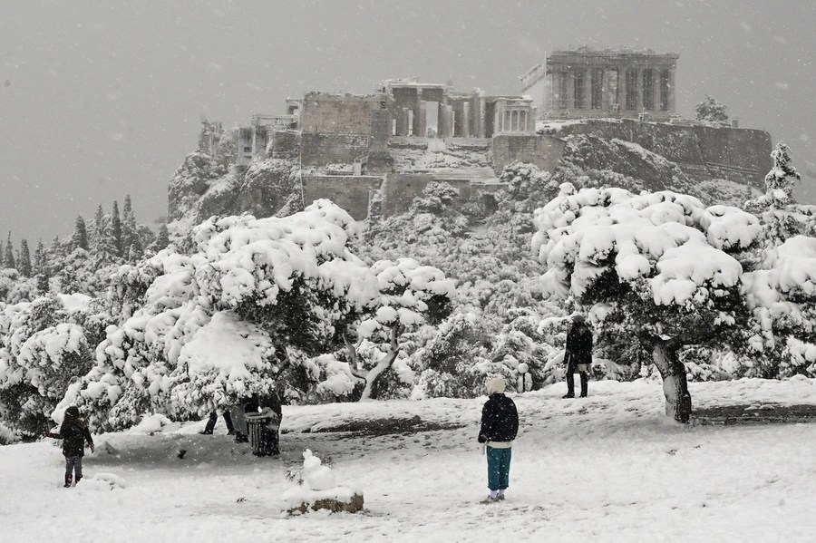 People play in the snow, with ancient Greek ruins visible in the background.
