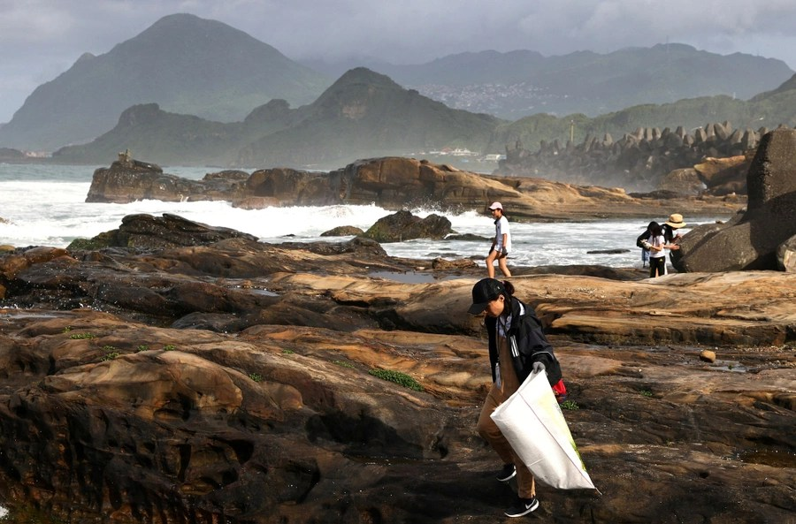 People walk along a rocky shoreline, collecting garbage.