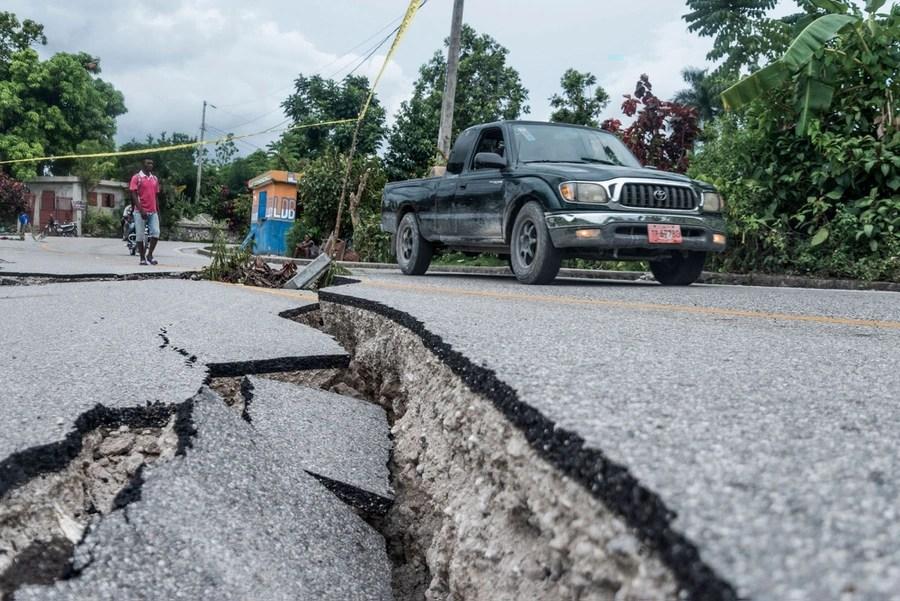 Il piccolo camion guida su una strada pesantemente danneggiata.