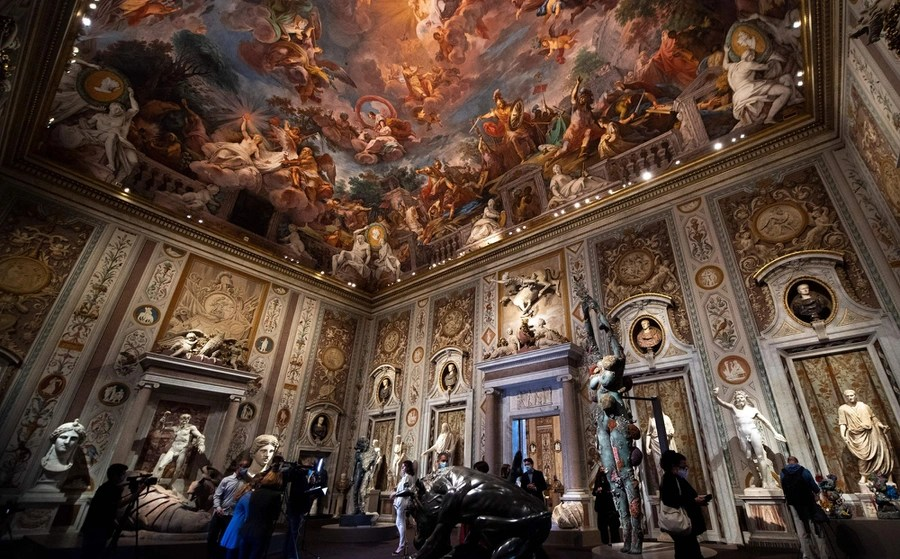 Sculptures stand inside an ornately decorated gallery room.
