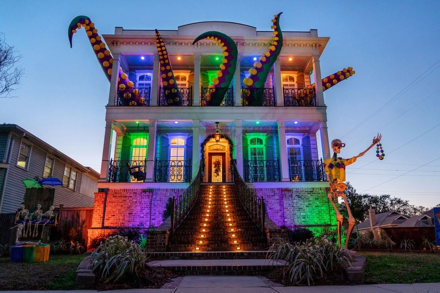A decorated two-story house appears to have tentacles emerging from its upper windows.