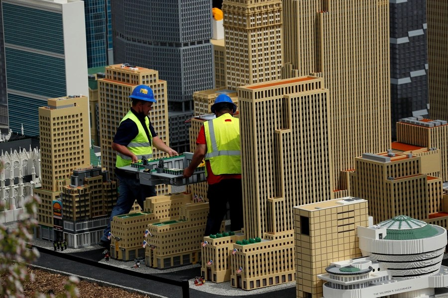 Workers carry a scale model of a structure among a cityscape of lego models.