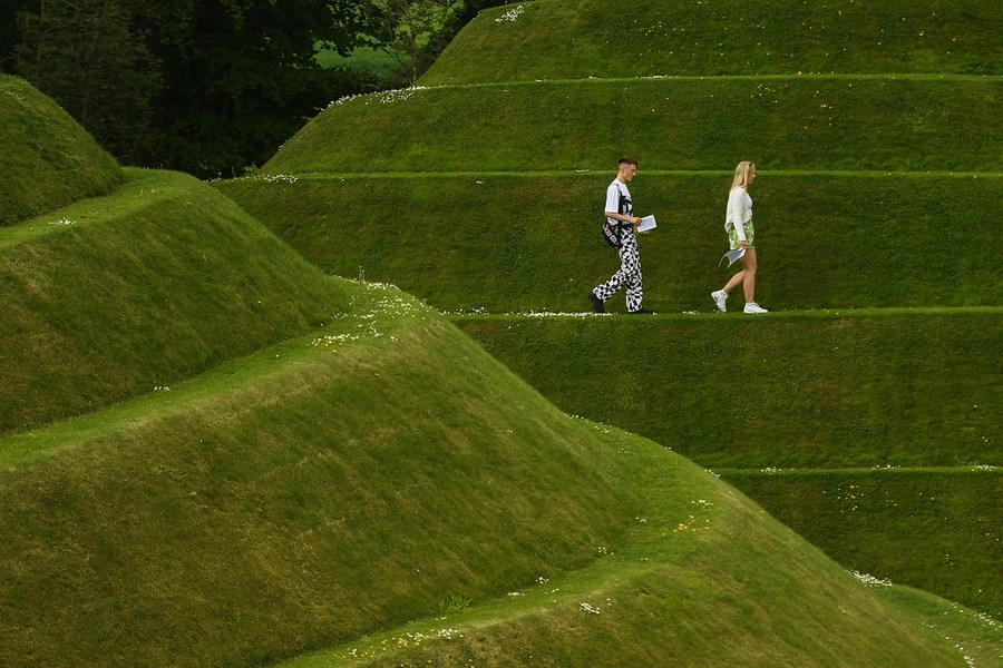 People walk on a terraced hillside covered in short grass.