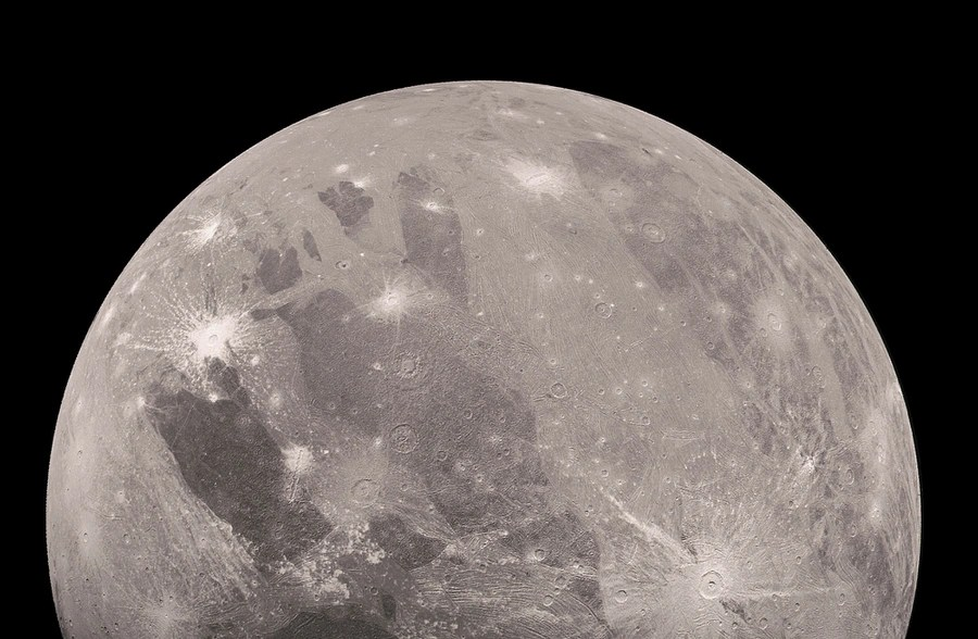 A close view of an enormous, gray, rocky sphere floating in space, pockmarked by craters and striations