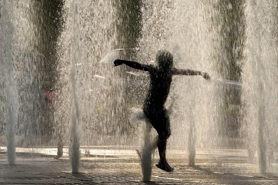 A boy leaps through fountains.