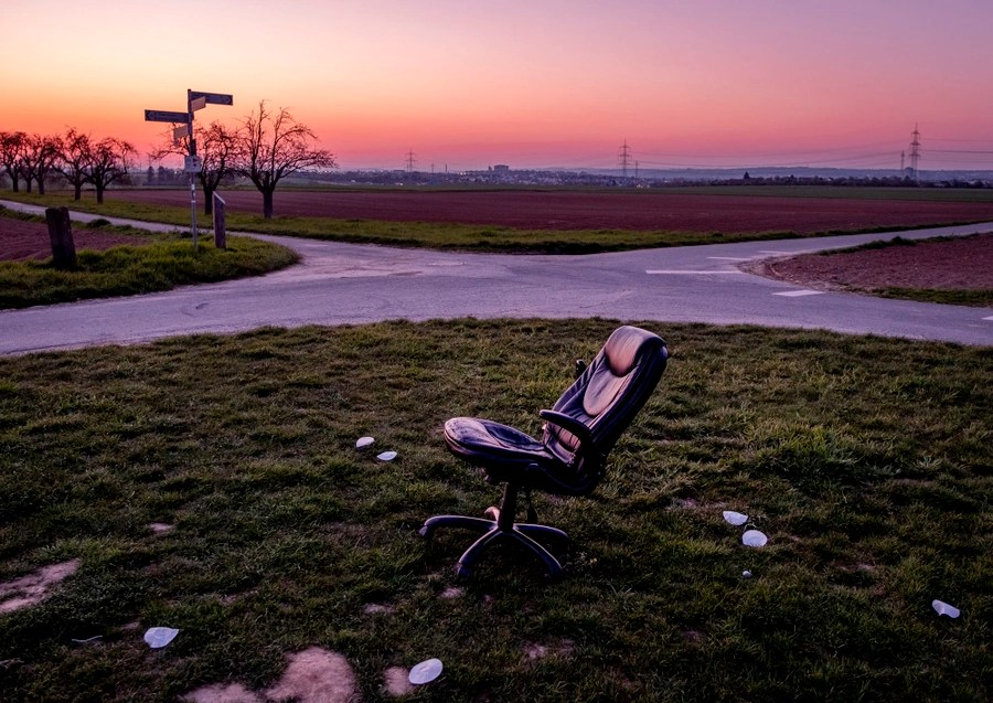 An office chair stands in a vacant lot.