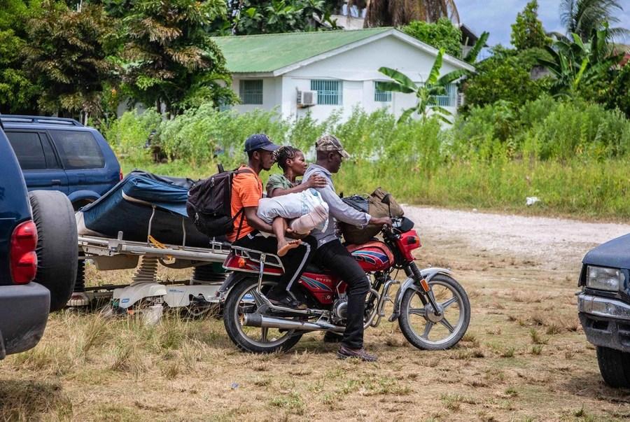 Due uomini su una moto trasportano una terza persona con un piede ferito.