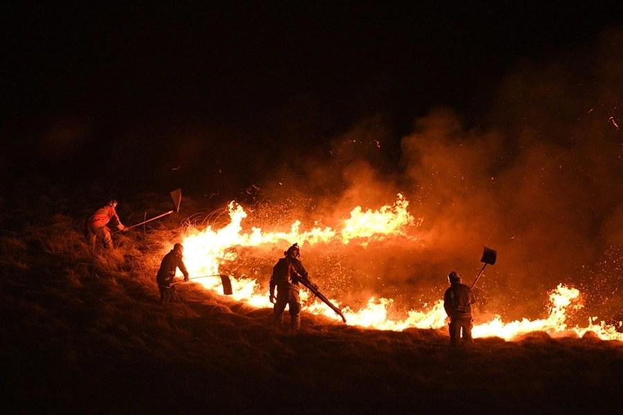 Firefighters battle a broad fire on a moor.