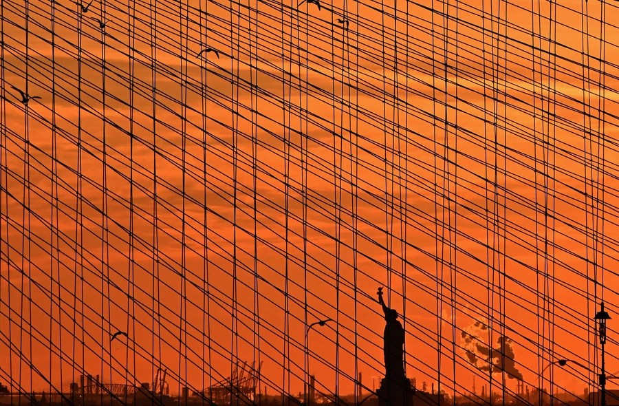A distant view of the Statue of Liberty, seen through bridge cables