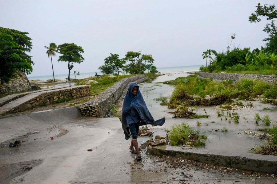 Un giovane cammina su un sentiero leggermente allagato.