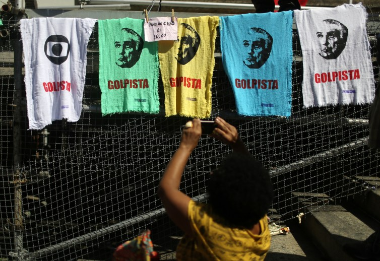 A woman hangs banners accusing Brazilian President Michel Temer of seizing power in a coup d'etat. Credit: Pilar Olivares/Reuters