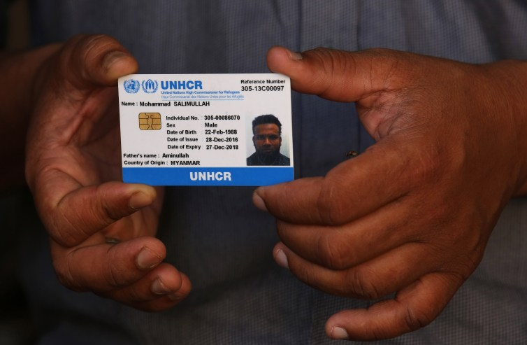 A Rohingya man shows his ID card given by the UNHCR in New Delhi, India. Credit: Rajat Gupta