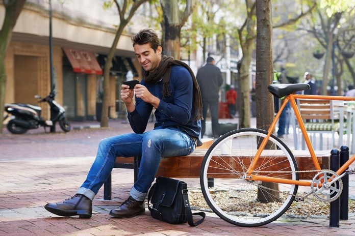 A young man taking a break from riding his bicycle to send a text message