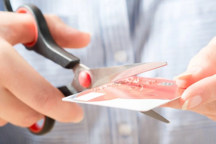Hands of a person cutting a credit card