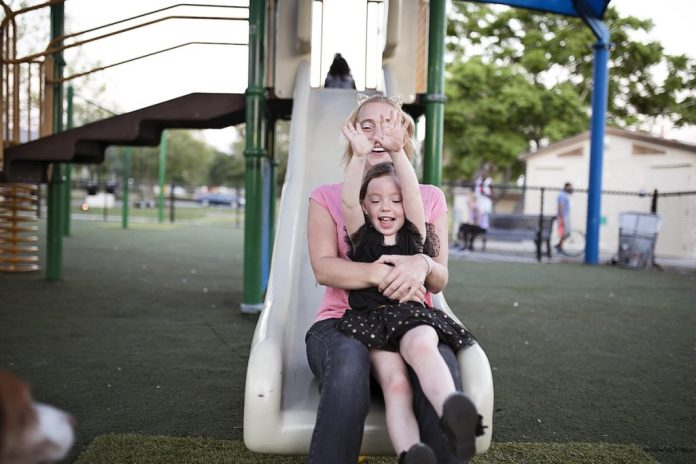 A mother slides down a slide with her daughter.