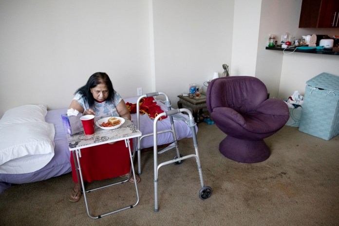 A woman eats while sitting on her bed.
