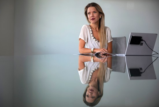 A businesswoman poses for a portrait with her laptop.