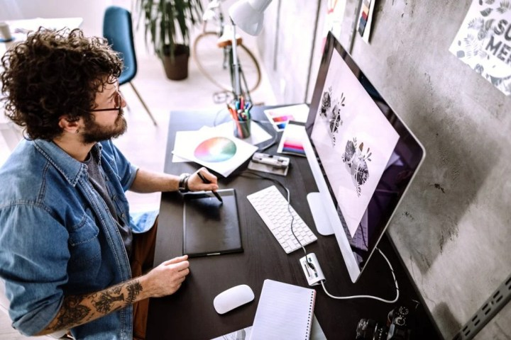 A man with curly hair and tattoos works on an illustration on his desktop computer.