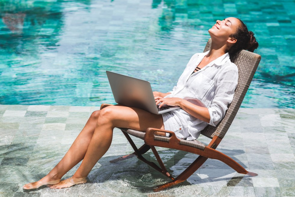A woman works on her laptop while dipping her feet into a pool.