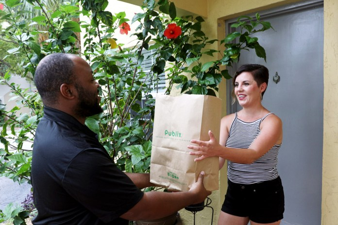 A woman with a pixie hair cut receives her Publix groceries from a Shipt driver.