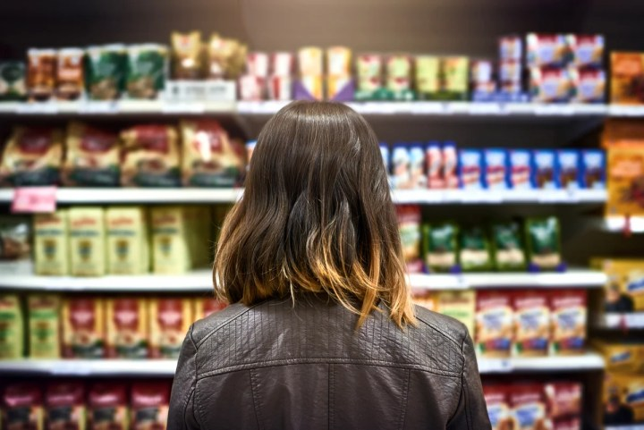 A woman looks at what to buy at the grocery store .