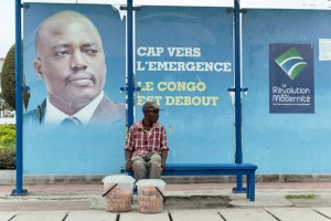 FILE PHOTO: A vendor sits at a bus stand with pictures of President Joseph Kabila in Kinshasa, Democratic Republic of Congo December 31, 2016. Credit: Reuters/Robert Carrubba/File Photo