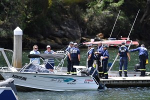 Australian Fire & Rescue personnel stand near their boats after visiting the scene where a seaplane crashed on Sunday killing six people, at Apple Tree Bay boat ramp located on the Hawkesbury River, north of Sydney in Australia, January 2, 2018. AAP/Mick Tsikas/via Reuters