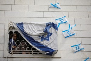 A Jewish settler youth looks out from a window covered with an Israeli flag hanging on a disputed building where about a hundred hard-line Jewish settlers have hunkered down, in the West Bank city of Hebron July 26, 2017. Credit: Reuters/Amir Cohen