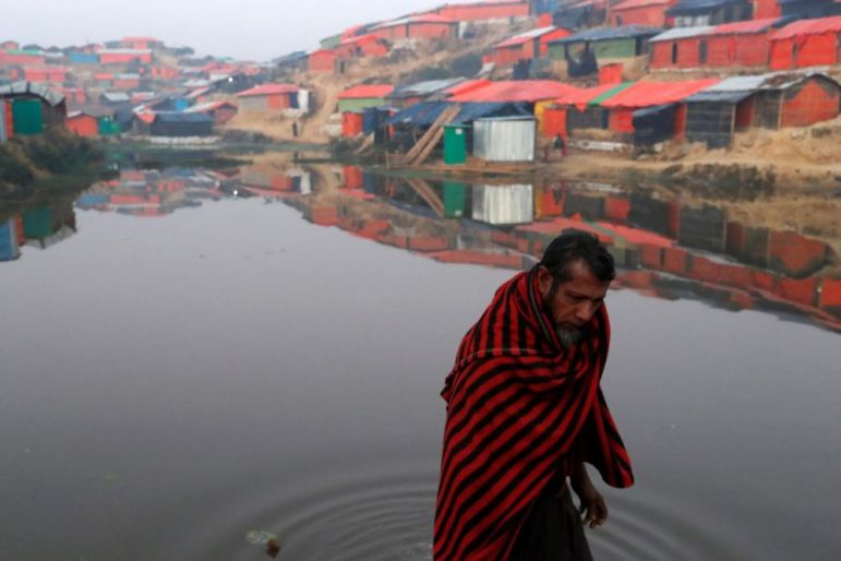 A Rohingya refugee walks next to a pond in the early morning at Balukhali refugee camp near Cox's Bazar, Bangladesh January 10, 2018. Credit: Reuters/Tyrone Siu
