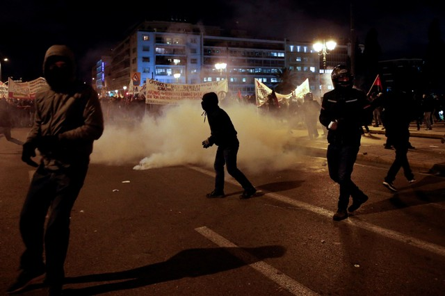Hooded protesters stand next to teargas smoke as they clash with riot police during a demonstration against planned government reforms that will restrict workers rights to strike in Athens, Greece, January 15, 2018. Credit: Reuters/Alkis Konstantinidis