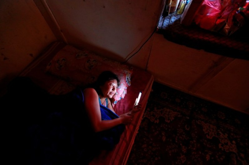 "Drayang dancer Lhaden, 38, checks her mobile phone as she rests at home in the capital city of Thimphu, Bhutan, December 16, 2017. Lhaden, a divorced mother-of-two, dances until midnight, and like thousands of her compatriots, is struggling to make ends meet. ""I'm not happy or sad about things, I have no other choice,"" she said. Lhaden, who earns $125 a month, is counting the pennies. ""I live in such a small flat so I can afford food and clothes."" Credit: Reuters/Cathal McNaughton"