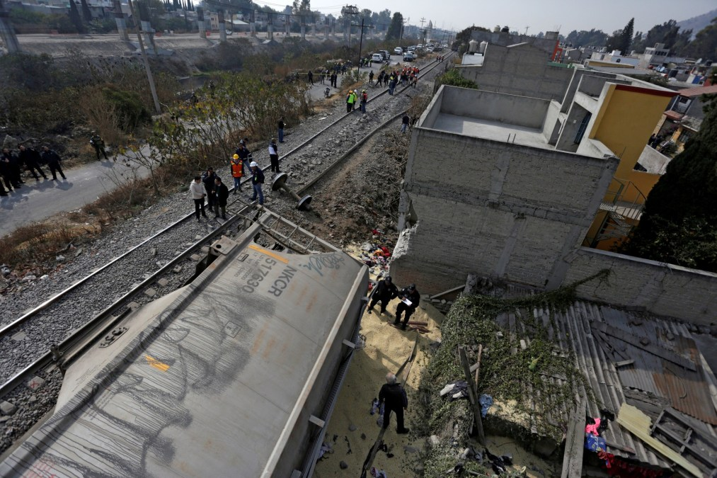 Security forces and railroad workers stand next to the car of a cargo train that ran off the tracks knocking a home in the municipality of Ecatepec, on the outskirts of Mexico City, Mexico January 18, 2018. Credit: Reuters/Daniel Becerril