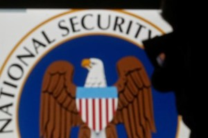 A man is silhouetted near logo of the US NSA in this photo illustration taken in Sarajevo March 11, 2015. Credit: Reuters/Dado Ruvic