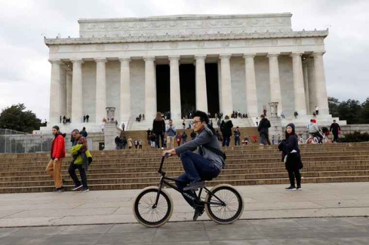 A man cycles in front of Lincoln Memorial in Washington, US, on the second day of Government shutdown, January 21, 2018. Credit: Reuters/Yuri Gripas