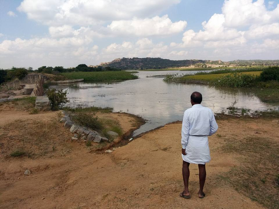 Ranga Reddy stands in front of the village pond that helps irrigate about four surrounding villages. Credit: Raksha Kumar