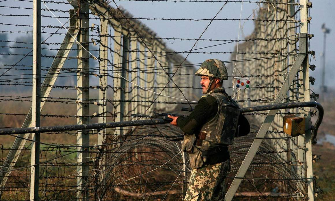 An Indian Border Security Force soldier patrols the fenced border with Pakistan in Suchetgarh, located southwest of Jammu and Kashmir. Credit: Reuters