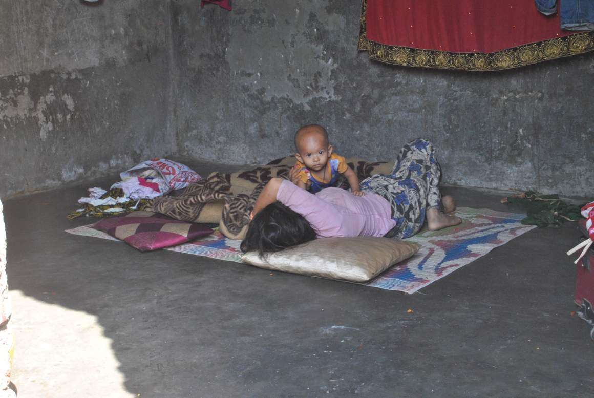 Ten-month-old Shafiqa plays with her mother in their hut in a settlement in Narwal, Jammu. Credit: Rohini Mohan