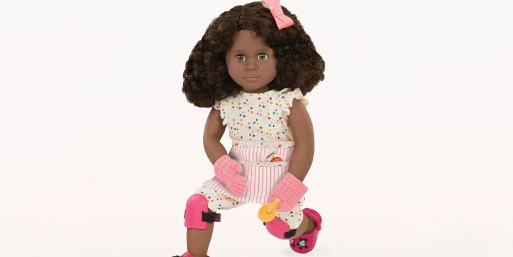 A Our Generation Deluxe Doll shown wearing a gardening outfit and holding a small shovel.