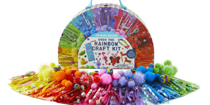 The Kid Made Modern Rainbow Craft Kit, shown with the contents of the box (pipe cleaners, pompom balls, and other craft items) arranged in front of the box.
