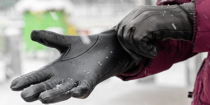 A person shown pulling the Kent Wang Deerskin glove over their hand, while snow falls.