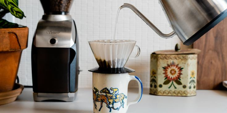 The Kalita Wave 185 Dripper, shown placed on a mug, with a person pouring a kettle of water into the filter.